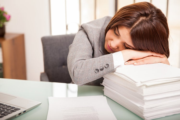 woman asleep on paper stack